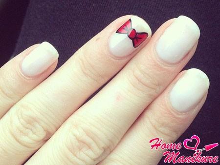 красивый красный бант на белых ногтях